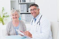Lycklig doktors- och kvinnligpatient i klinik Arkivfoton