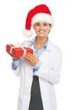 Lycklig doktorskvinna i ask för gåva för jul för santa hatt hållande Arkivbild