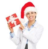 Lycklig doktorskvinna i ask för gåva för jul för santa hattvisning Royaltyfri Fotografi