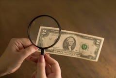 Lycklig dollar i hand till och med ett förstoringsglas royaltyfri fotografi