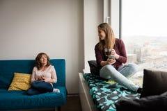 Lycklig dotter och moder med tekoppar hemma Arkivfoto