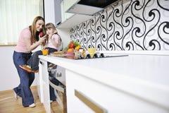 Lycklig dotter och mom i kök Arkivbilder