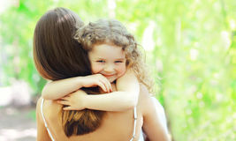 Lycklig dotter som kramar modern i varm solig sommardag på naturen