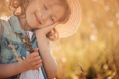 Lycklig drömma hållande bukett för barnflicka i sommar Arkivfoton