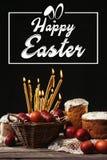 Lycklig easter inskrift i ram, brännande stearinljus, easter kakor och målade ägg Arkivbilder