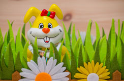 Lycklig easter kanin i ett rede med gräs och blomman Arkivfoto