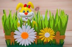 Lycklig easter kanin i ett rede med gräs och blomman Arkivbilder