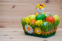 Lycklig easter kanin med ägg i en korg på Royaltyfri Fotografi