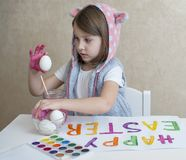 Lycklig easter liten flickamålare i rosa kaninöron med färgrika målade ägg En unge som förbereder sig för påsk målad hand royaltyfri foto