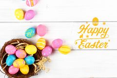 Lycklig easter text inte rosa, gula och blåa kulöra easter ägg på den vita träbakgrunden stock illustrationer