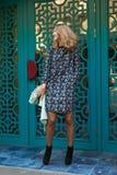 Lycklig elegant kvinna nära blå dörr royaltyfria bilder