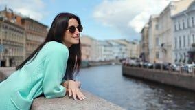 Lycklig elegant turist- kvinna som beundrar floden som omges av stadssikten som har positiv sinnesrörelse stock video