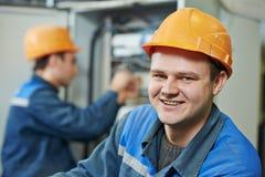 Lycklig elektrikerteknikerarbetare arkivbild