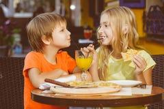 Lycklig eller tillfredsställd pojkebreddflicka som äter pizza och Royaltyfri Bild