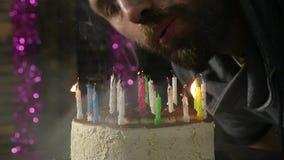 Lycklig emotionell man som ut blåser stearinljusen på en födelsedagkaka, släckta stearinljus stock video