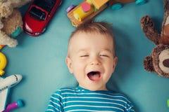 Lycklig en årig pojke som ligger med många flotta leksaker Arkivfoto