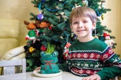 Lycklig en årig pojke som ligger med många flotta leksaker på den blåa filten arkivbilder