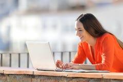 Lycklig entreprenörhandstil på bärbara datorn i en balkong royaltyfria bilder