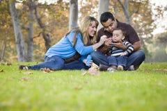 Lycklig etnisk familj för blandat lopp som spelar med bubblor i parkera royaltyfria bilder