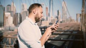 Lycklig europeisk affärsman som använder det mobila kontoret app för smartphone på den Brooklyn bron som vänder därefter i väg fr lager videofilmer