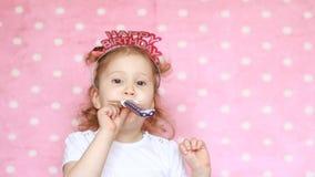 lycklig födelsedag deltagare Beröm Det roliga barnet som blåser hornet som ler, har gyckel, skrattar, ferier och firar Närbild arkivfilmer