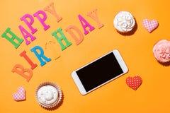 Lycklig födelsedag för ord med muffin och smartphonen på gul backg Arkivfoto