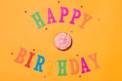 Lycklig födelsedag för ord med muffin på gul bakgrund Arkivfoton