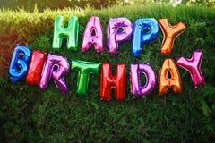 Lycklig födelsedag! Inskriften av färgrika ballonger, garnering på ett festligt trädgårdparti på bakgrunden av en grön häck royaltyfria foton