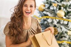 Lycklig för öppningsshopping för ung kvinna påse nära julträd arkivbild