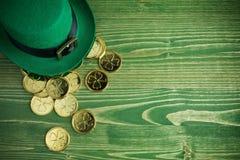 Lycklig för dagtroll för St Patricks hatt med guld- mynt på grön träbakgrund för tappning arkivbild