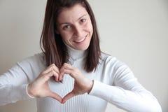 Lycklig för danandehjärta för ung kvinna form med händer Arkivbild