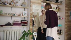 Lycklig för hattframdel för kvinna montering stucken spegel i textilseminarium stock video