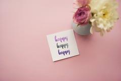 Lycklig ` för ` som är skriftlig i kalligrafistil på papper med buketten av rosa vita krysantemum för rosor och Lekmanna- lägenhe Arkivfoto