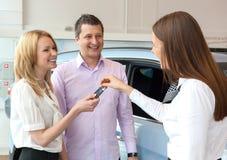 Lycklig försäljare som räcker över biltangenter till den attraktiva unga familjen Arkivbilder
