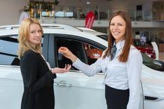 Lycklig försäljare som räcker över biltangenter till den attraktiva unga kvinnliga ägaren Royaltyfria Foton
