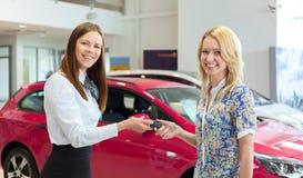 Lycklig försäljare som räcker över biltangenter till den kvinnliga ägaren av den nya bilen Royaltyfria Foton