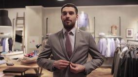 Lycklig försökande dräkt för ung man på klädlagret lager videofilmer