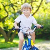 Lycklig förskole- ungepojke som har gyckel med att rida hans cykel Arkivfoto