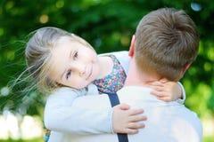 Lycklig förtjusande liten flicka som kramar omfamna hennes fader Royaltyfri Fotografi