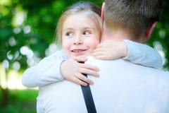 Lycklig förtjusande liten flicka som kramar omfamna hennes fader Arkivfoton