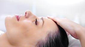 Lycklig förtjusande ung kvinna för sidosikt med perfekt hud som tycker om massage på skönhetbrunnsortsalongen stock video