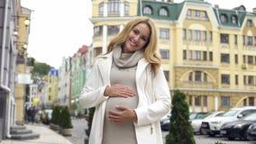 Lycklig förväntande kvinna som ser kameran och ler och att slå buken, moderskap arkivbilder