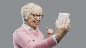 Lycklig förvånad hög dam som använder en digital minnestavla arkivfoton