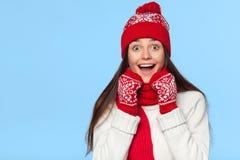 Lycklig förvånad kvinna som från sidan ser i spänning Julflicka som bär den stack varma hatten och tumvanten som isoleras på blåt arkivfoton