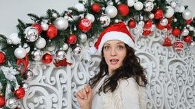 Lycklig förvånad ung kvinna i den Santa Claus hatten som tillbaka vänder och ser kameran med intresse i jul arkivfilmer