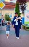 Lycklig fader, affärsman som går med ungar på stadsgatan Arkivbilder
