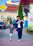 Lycklig fader, affärsman som går med ungar på stadsgatan Arkivbild