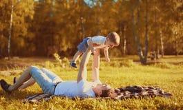 Lycklig fader med barnsonen som har roligt hållande på händer som ligger på gräs, foto för familj för höstafton soligt arkivfoto