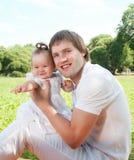 Lycklig fader med dottern i parkera fotografering för bildbyråer