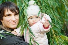 Lycklig fader med dottern på bakgrund av det gröna trädet Fotografering för Bildbyråer